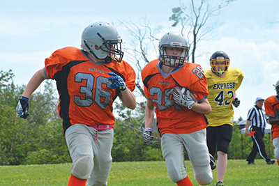 Orangeville's Lucas Snowdon runs blocking for ball carrier Jack Roud during Sunday's (July 9) Bantam game against the TNT Express at Westside Secondary School. The Outlaws got off to a good start with two early touchdowns and finished the game with a 40-6 win.